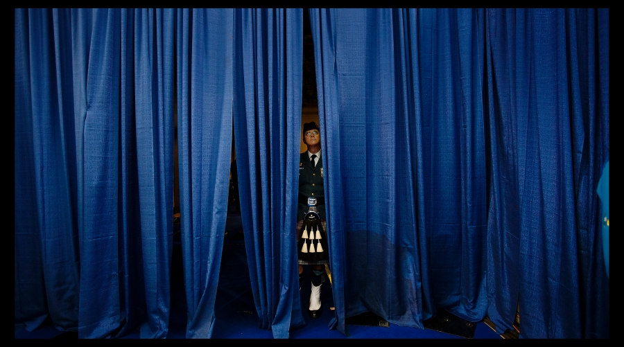 Canadian bag piper watches the 2013 Ford World Curling Championships from behind a curtain