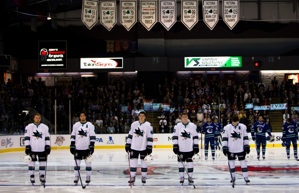 The San Jose Sharks starting lineup stands on the blue line while listening to the Canadian and American National Anthems prior to facing off against the Vancouver Canucks in their Kraft Hockeyville exhibition game on September 21, 2015 at the Q centre in Colwood B.C. Canada. (Photo by Kevin Light/SanJose Sharks)