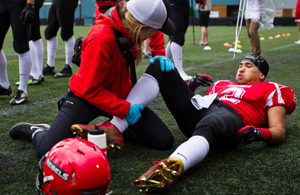 Westshore Rebels defensive back Jordan Bosse is attended to by Athletic Therapist Molly Atkin during a game versus the Kamloops Broncos at Westhills Stadium in Langford B.C. on Saturday August 29, 2015.