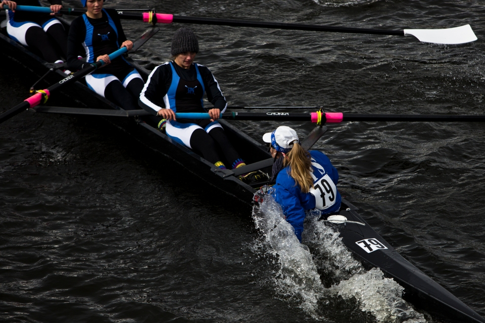 Coxswain Sarah Brown pushes her right arm into the water attempting to turn her McCallie Women's Youth Eights crew around Weeks Footbridge faster at the Head of the Charles rowing regatta in Boston Massachusetts on October 18th 2015.