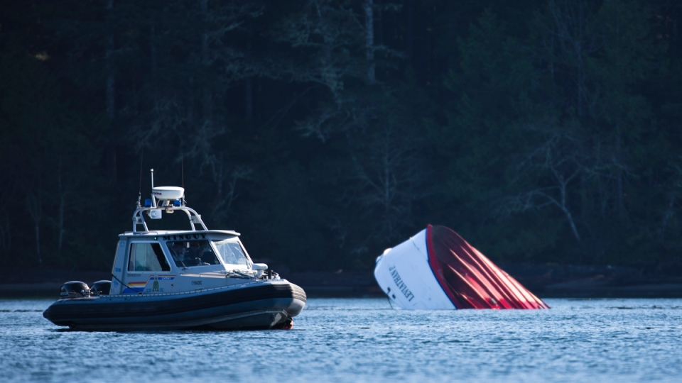 An RCMP boat carrying divers sits beside the capsized whale watching boat Leviathan II in Tofino, British Columbia on October 26, 2015. Many of the passengers were sightseeing on one side of the upper deck when a wave hit from the opposite side, flipping the boat and sending all 27 passengers and crew into the water, killing five of the passengers.