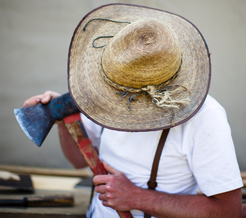 A man in a large hat looks at his axe.