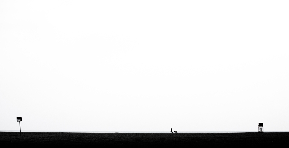 A man walks his dog at Woodbine beach in Toronto, Ontario on December 7th, 2015