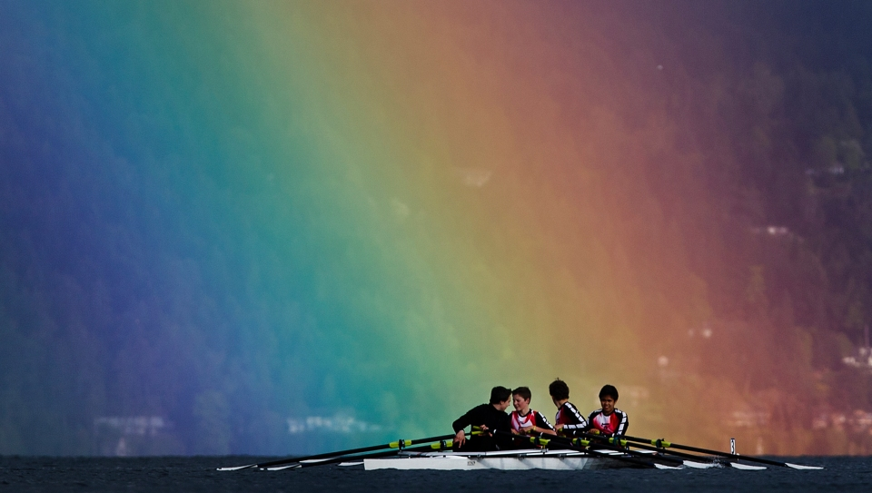 Rowers paddle beneath a rainbow in Mill Bay, British Columbia Canada.