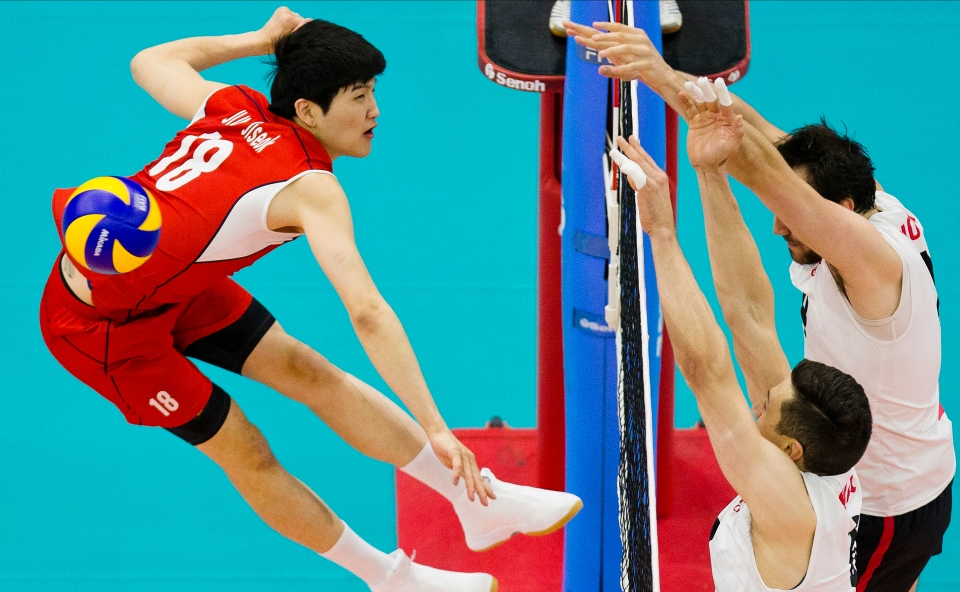 Jiseok Jung (18) of Korea is blocked by Adam Simac (8) and Nicholas Hoag (4) of Canada Kevin Light Photo
