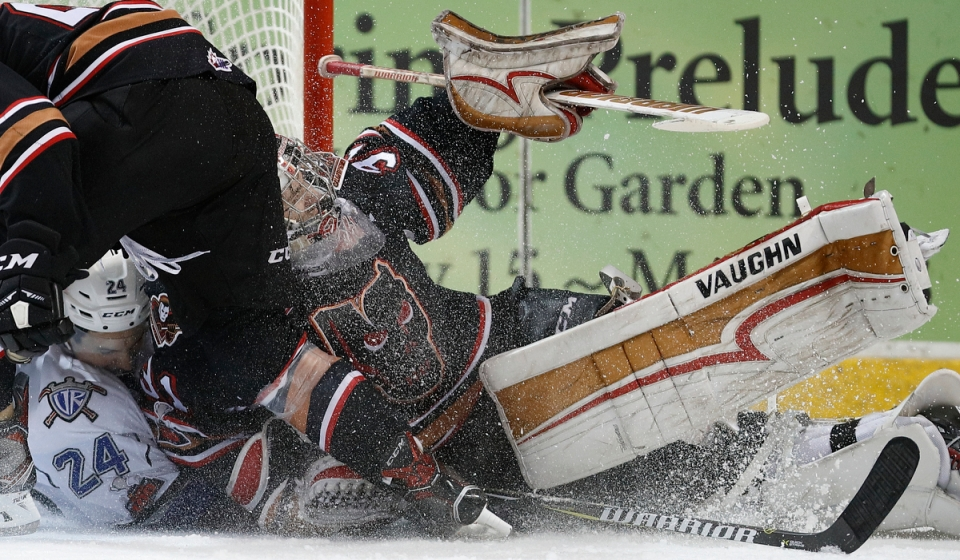 Victoria Royals forward Lane Zablocki crashes into Calgary Hitmen goaltender Nick Schneider .JPG ©KevinLightPhoto
