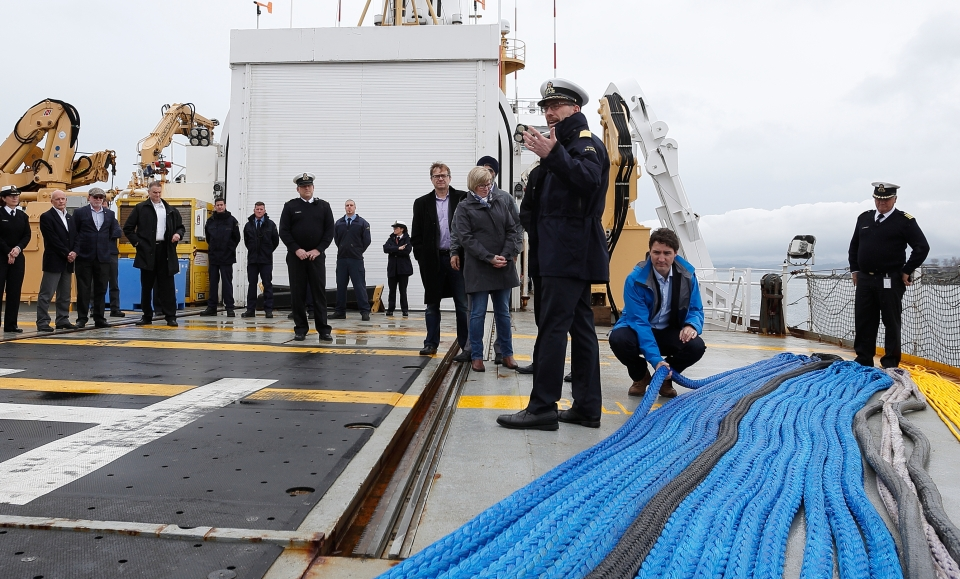 Canada's Prime Minister Justin Trudeau, looks at a ropes that are part of emergency toe kits for broken down vessels that need assistance prior to meeting with Canadian coast guard workers in Victoria